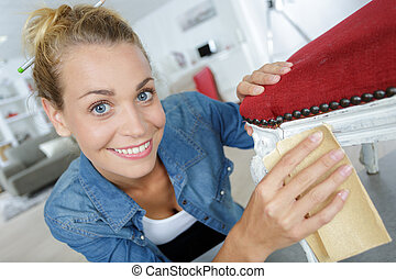 happy hardworking woman sandinfg a chair