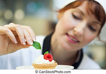 Happy head chef putting mint leaf on little cake in ...