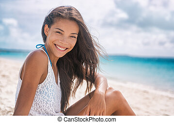 Happy healthy Asian woman smiling on beach vacation lifestyle. Young multiracial chinese girl relaxing in summer outdoor travel holidays. Portrait of beautiful lady in tropical background