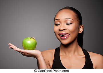 Happy healthy black asian woman with delicious apple