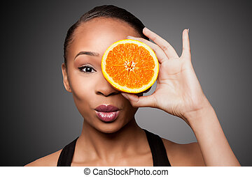 Happy healthy black asian woman with orange fruit