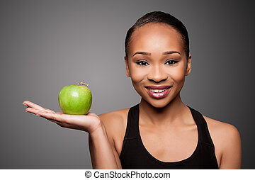 Happy healthy black asian woman with apple