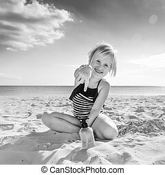 happy healthy child in swimwear on beach pointing at sun screen