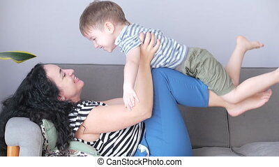 Happy healthy family young mom lifting cute little child son up playing plane on sofa at home, funny kid boy flying in mothers practice sport.