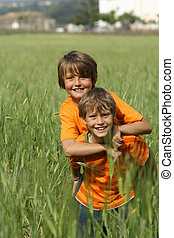 happy healthy fit active children or kids playing piggyback outdoors