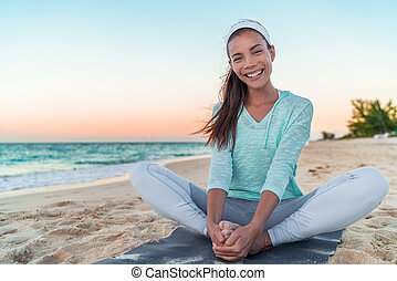 Happy healthy lifestyle yoga girl stretching legs exercise on morning fitness training. Asian woman smiling on beach