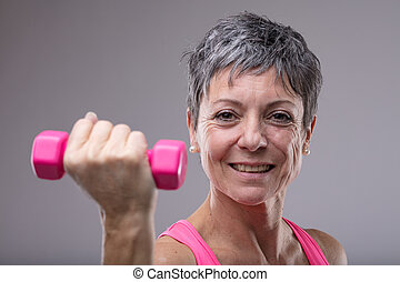 Happy healthy middle-aged woman working out