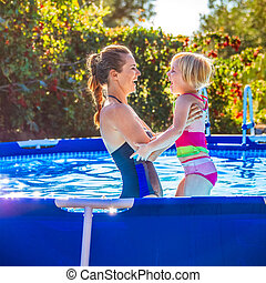 happy healthy mother and child in swimming pool playing -...