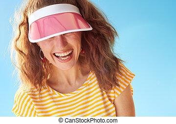 happy healthy woman against blue sky hiding behind sun visor...