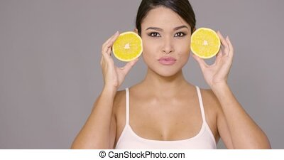 Happy healthy woman holding up sliced oranges