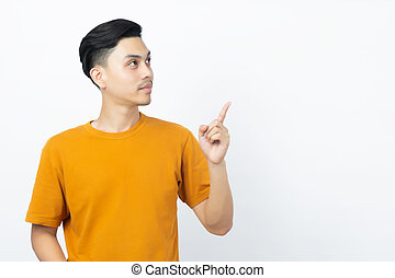 Happy healthy young Asian man smiling with his finger pointing up to copyspace on white background