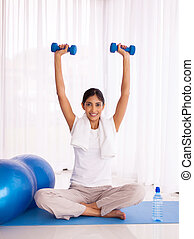 young indian woman lifting dumbbells