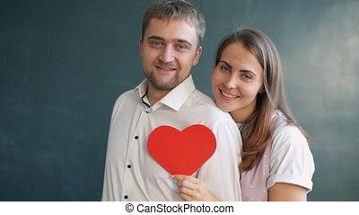 Happy heterosexual couple holding heart shape valentine card...