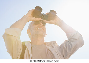 Happy hiker looking through binoculars