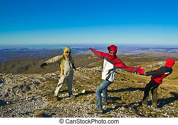 Happy hikers in mountains playing with strong wind