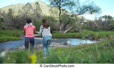 Happy hikers women jumping at the mountain river in beautiful landscape nature with mountains trees in slow motion.