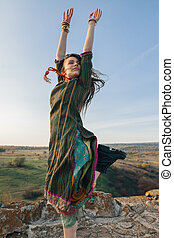 Happy hippie woman jump on top of mountain with hands up