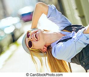 Happy hipster girl having fun on city street