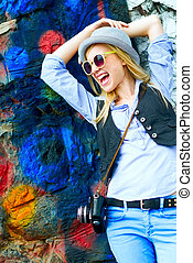 Happy hipster girl looking on copy space against urban wall
