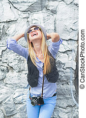 Happy hipster girl rejoicing against rocky wall outdoors