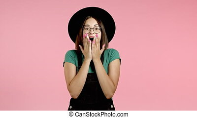 Happy hipster girl, she is very glad, because of excellent news. Wow effect. Surprised excited happy woman in hat on pink background.