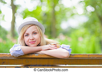 Happy hipster girl sitting in the park