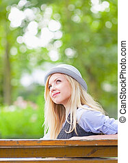 Happy hipster girl sitting on bench in the park and looking on copy space
