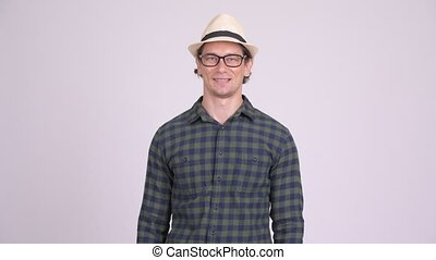 Happy hipster man smiling with arms crossed - Studio shot of...
