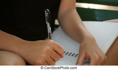 Happy hipster young asian woman writing into her diary in...