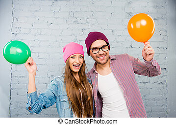 Happy hipster young man and woman celebrating with balloons