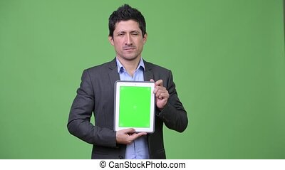 Happy Hispanic businessman showing digital tablet - Studio...