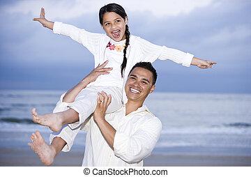 Happy Hispanic dad and girl having fun on beach