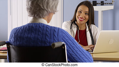 Happy Hispanic doctor talking with senior patient