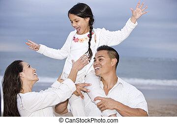 Happy Hispanic family and girl having fun on beach - Happy...