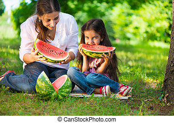 Happy hispanic family eating watermelon