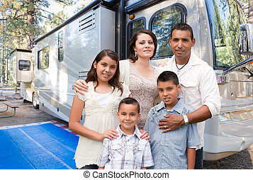 Happy Hispanic Family In Front of Their Beautiful RV At The Campground.