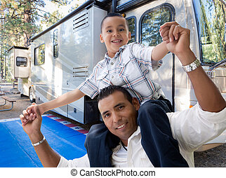 Happy Hispanic Father and Son In Front of Their Beautiful RV At The Campground.