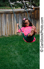 Happy Hispanic female child on swin