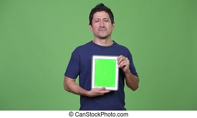 Happy Hispanic man showing digital tablet - Studio shot of...