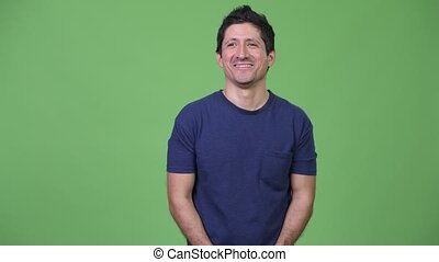 Happy Hispanic man thinking against green background -...
