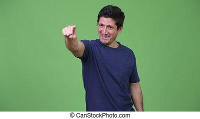 Happy Hispanic man thinking while pointing finger - Studio...