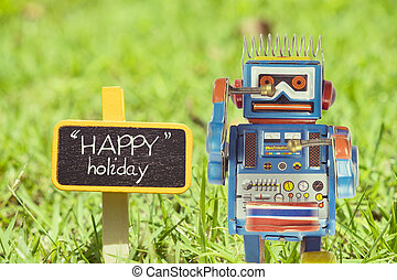 Happy Holiday word. Toy robot with sign on green grass.
