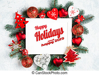 Happy Holidays and happy 2019 text with Holiday Evergreen Branches and Berries in Corner Over Rustic Wooden Background