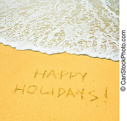 happy holidays written in the sandy beach