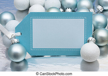 A blank Christmas gift tag sitting with glass balls on a shiny background, happy holidays present