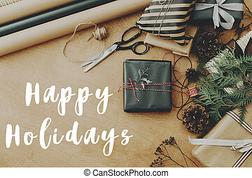 Happy Holidays text sign on stylish christmas lat lay with gift box, pine branch and scissors, rustic presents, thread, pine cones on wooden table. Season's greetings card