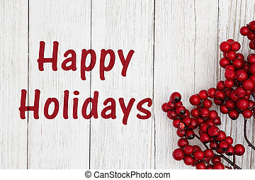 Happy holidays text with red berry branch on weathered whitewash textured wood