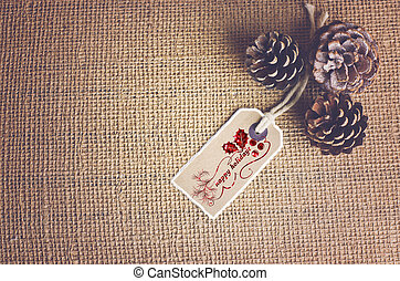 Happy holidays text written on label on nature colour fabric background. Pine cones in a corner with copy spaced.
