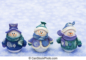 Three snowman sitting together on a snowflake background, happy holidays