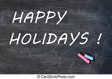 Happy holidays written on a smudged blackboard with chalk